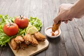 stock photo of dipping  - Hand dunk chicken hot wings in dipping sauce on wooden - JPG