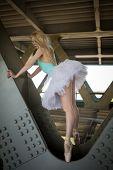 stock photo of tutu  - Graceful ballerina in white tutu in the industrial background of the bridge - JPG