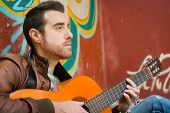 stock photo of rockabilly  - man with guitar in the street - JPG
