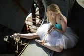 stock photo of tutu  - Ballerina sitting on the edge of the bridge - JPG
