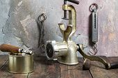 pic of outdated  - Outdated items Kitchen steelyard scissors manual grinder tea strainer can can opener on a wooden table against a wall with an old plaster - JPG