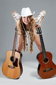 picture of cowgirl  - Sesy cowgirl in cowboy hat with a nylon string acoustic guitar - JPG