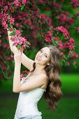 image of allergies  - Young spring fashion woman in spring garden Springtime Summertime Trendy girl in the flowering trees in then at sunset in spring summer landscape background Allergic to pollen of flowers Allergy 