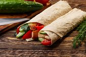 picture of shawarma  - Traditional shawarma wrap with chicken and vegetables near cutting table - JPG