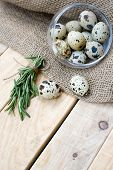 stock photo of quail  - Quail eggs a bunch of rosemary and burlap are on the unpainted wooden background - JPG
