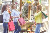 foto of flower shop  - Happy Shopping Female Friends with bags watching flowers in the street shop - JPG
