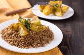 picture of buckwheat  - Buckwheat porridge with baked onions on a wooden table - JPG