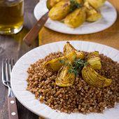 stock photo of buckwheat  - Buckwheat porridge with baked onions on a wooden table - JPG