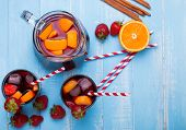 picture of sangria  - Refreshing strawberry sangria on blue colored wooden background top view - JPG