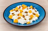 picture of curd  - Granular curd in blue glass plate mixed with peaches and raisins on wooden table - JPG