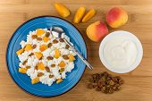 picture of curd  - Curd in blue plate with peaches and raisins bowl with sour cream on bamboo board top view - JPG