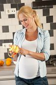 pic of pregnant woman  - Attractive pregnant woman standing in the kitchen peeling an apple - JPG