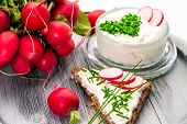 stock photo of chive  -  A bowl with curd and radish and a heart shaped chives decoration and brown bread - JPG