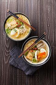 stock photo of noodles  - Asian Miso ramen noodles with egg tofu and enoki in bowls on gray wooden background - JPG