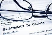 stock photo of summary  - Close up of reading glasses on Summary of claim - JPG