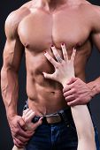 Sex Concept - Female Hands Touching Muscular Man Over Grey poster