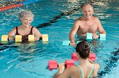 Senior couple in training session of aqua aerobics using dumbbells in swimming pool. Mature man and  poster