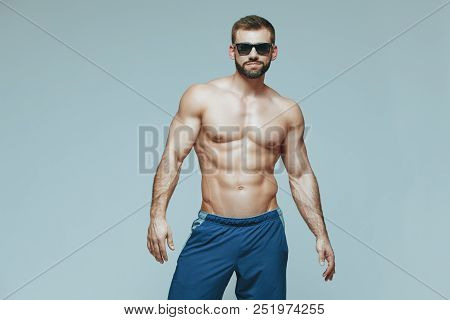 poster of Bodybuilder Posing. Beautiful Sporty Guy Male Power. Fitness Muscled In Blue Shorts And Sunglasses.