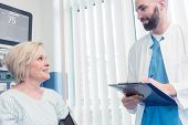 Doctor talking to patient in recovery room of hospital after awaking from treatment or surgery poster