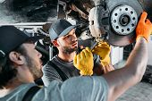 Professional Amle Mechanics Repairing Car Without Wheel In Auto Repair Shop poster