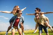 leisure, people and friendship concept - happy teenage friends having fun outdoors in summer poster
