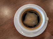 A White Cup Of Black Coffee With Creama Put Over Brown Wooden Table poster