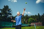 Side View Smiling Child Catching Ball While Holding Sport Tool In Hand. Glad Kid Playing Tennis Conc poster
