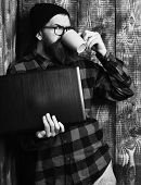 Bearded Man, Long Beard. Brutal Caucasian Serious Unshaven Hipster Holding Laptop Drink From Mag Or  poster