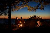 Night Camping At Lake. Tourist Tent And Back View Of Young Couple, Boy And Girl At Campfire Under Tr poster