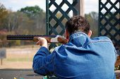 image of shooting-range  - Man in blue jeans jacket takes aim with rifle - JPG