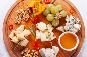 Cheese Plate. Delicious Cheese Mix With Walnuts, Honey, Grapes On Wooden Table. Tasting Dish On A Wo poster