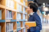 Young Asian Man Student Choosing Book In Public Library. Male Researcher Looking For Textbook On Boo poster