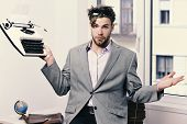 Man With Puzzled Face Types Business Report. Young Author Or Editor Holds Old Typewriter On Window B poster