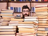 Man, Nerd On Surprised Face Between Piles Of Books In Library, Bookshelves On Background. Teacher Or poster