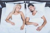 Top View Of Young Couple Sleeping In Bed At Home. Healthy Sleep Concept. Snore, Sleep, Apnea, Couple poster