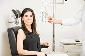 Portrait Of Happy Young Woman Sitting Behind Phoropter During Eye Exam While Looking At Camera And M poster