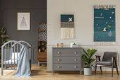 Real Photo Of A Grey Cupboard Standing Between A Crib, And An Armchair And Plant In Spacious Childs poster