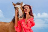 A hispanic brunette model rides a horse on a Caribbean beach poster