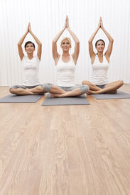 image of yoga mat  - An interracial group of three beautiful young women sitting cross legged in a yoga position at a gym - JPG