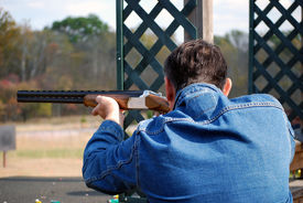 picture of shooting-range  - Man in blue jeans jacket takes aim with rifle - JPG