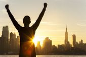 Silhouette of a successful woman or girl arms raised celebrating at sunrise or sunset in front of th
