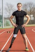 stock photo of paralympics  - Athlete with handicap stands on a race track - JPG