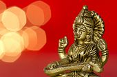 picture of saraswati  - close up of a Hindu deity statue with lights in the back on red background - JPG