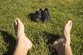 Постер, плакат: ноги отдохнуть в траве с его обувь