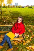 foto of 11 year old  - Autumn portrait of a 11 years old girl sitting on the bench in the park after school with paper folder - JPG