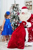 stock photo of saint-nicolas  - Saint Nicolas gives Christmas gifts to the little girl - JPG