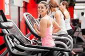 picture of treadmill  - Pretty girl working out in a treadmill at the gym and smiling - JPG