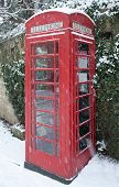 stock photo of english ivy  - English red telephone box in winter snow against an ivy clad Cotswold stone wall - JPG