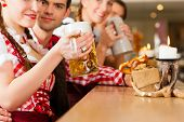 picture of stein  - Young people in traditional Bavarian Tracht in restaurant or pub with beer and steins - JPG
