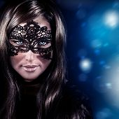 Closeup portrait of beautiful stylish woman wearing mask, luxury New Year party, masquerade in Chris